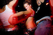 "Moonlite Bunny Ranch brothel sex workers Cutie Christina, left, and Bella Star, center, dance at a nightclub in Mound House, NV on Wednesday, July 26, 2006...The Moonlite Bunny Ranch brothel in Mound House, Nevada - just a few miles from the state capital in Carson City - first opened in 1955. The Ranch is a legal, licensed brothel owned by Dennis Hof. It's featured in the HBO series ""Cathouse."""