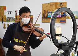 BEIJING, April 19, 2020  A staff member plays the violin during a live stream at a musical instruments producing company in Donggaocun Town of Pinggu District in Beijing, capital of China, April 19, 2020. The town's violin producing companies have orderly resumed work and production in recent days. However, influenced by the COVID-19, export orders of those companies have decreased. To cut losses, some of them try to sell the violins through online live stream. (Credit Image: © Ren Chao/Xinhua via ZUMA Wire)