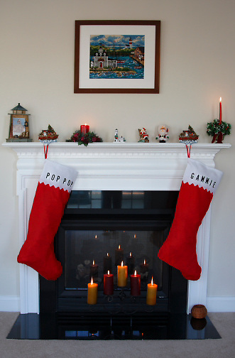 fireplace, mantle decorated for Christmas; 2 very large grandparents stockings; lighted candles