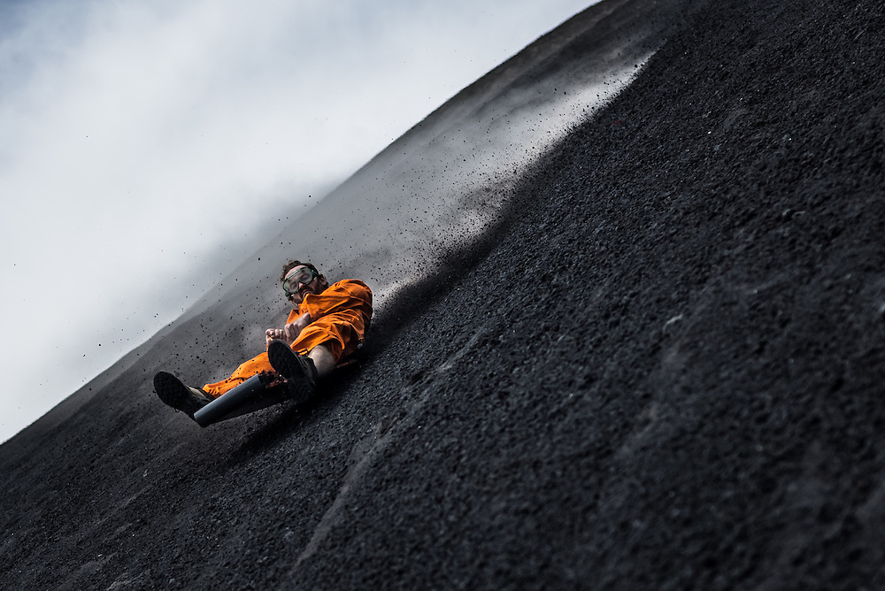 LEON, NICARAGUA - SEPTEMBER 18, 2014:  David Edwards, 29, a tourist from Tasmania, Australia volcano boarding down Cerro Negro volcano. Boarders can reach speeds of up to 95 kilometers per hour. Guided tours are available from $29 USD to board down the volcano, located an hour outside of Leon. PHOTO: Meridith Kohut