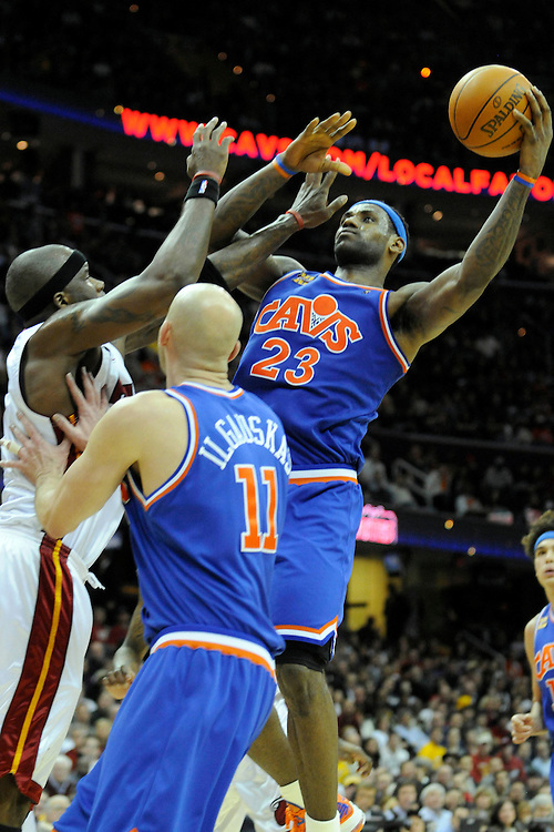 Feb 4, 2010; Cleveland, OH, USA; Cleveland Cavaliers forward LeBron James (23) shoots over Miami Heat center Jermaine O'Neal (7) and Cleveland Cavaliers center Zydrunas Ilgauskas (11) during the  fourth quarter at Quicken Loans Arena. The Cavaliers beat the Heat 102-86. Mandatory Credit: Jason Miller-US PRESSWIRE