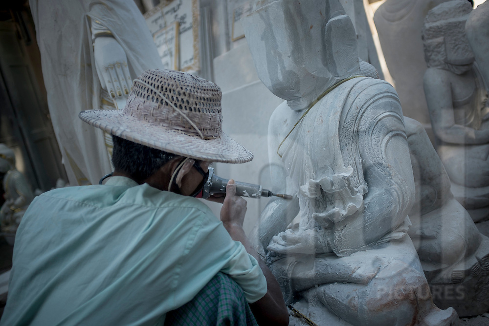 A man carves a Buddha statue along the street in Mandalay, Myanmar, Southeast Asia