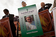 Banner-carrying Catholic pilgrims awaits arrival of Pope at Hyde Park rally during Pope Benedict XVI's papal tour of Britain 2010, the first visit by a pontiff since 1982. Taxpayers footed the £10m bill for non-religious elements, which largely angered a nation still reeling from the financial crisis. Pope Benedict XVI is the head of the biggest Christian denomination in the world, some one billion Roman Catholics, or one in six people. In Britain there are about five million Catholics but only a quarter of Catholics regularly attend Sunday Mass and some churches have closed owing to spending cuts.