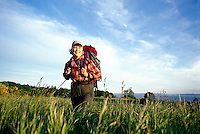 A smiling mature woman hiking with a backpack on across a field of high grass.
