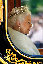 © Licensed to London News Pictures. 27/05/2015. London, UK. Queen Elizabeth II being driven down The Mall in a horse drawn carriage after attending the State Opening of Parliament on May 27, 2015 in London. In a speech to Members of Parliament and Peers in The House of Lords, Queen Elizabeth II officially opens a new session of parliament, which sets out the government's agenda and legislation for the coming year. Photo credit : Tolga Akmen/LNP