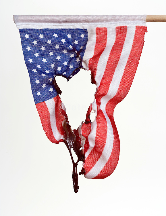 American flag with an hole burned in it against a white background