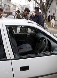 Policemen inspect a damaged vehicle at the shootout site in southwest Pakistan's Quetta, December 17, 2012, Photo by Imago / i-Images...UK ONLY