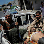 A group of rebel fighters rush to safety a injured comrade shot by a pro-Gaddafi snipper in central Zawiyah.