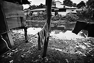 Clothes hanging out to dry by the polluted river. During heavy rain the water rises above this level and almost all the way into the houses.