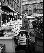 Moore Street, Dublin.      (J97)..1975..23.12.1975..12.23.1975..23rd December 1975..For well over a hundred years Moore Street has served the citizens of Dublin. The longest running open air fruit and vegatable market offers value for money,particularly to those where money is in short supply. Predominately a fruit and veg market there are several traders who sell fish and seasonal goods, as illustrated by the photographs showing turkeys and holly wreaths being sold on the run up to Christmas..Pictured, a trader catches her breath at her stall. Some seasonal holly wreaths are shown to the right of the photo.
