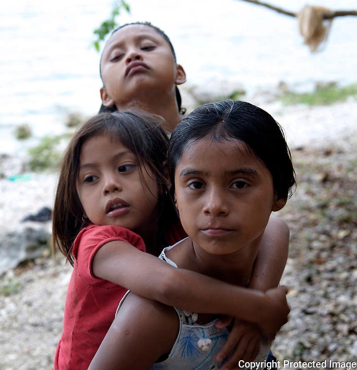 3 Cousins hugging by the lake in San Pedro, Guatemala