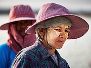 22 FEBRUARY 2017 - BAN LAEM, PETCHABURI, THAILAND: A salt field worker wearing a floppy hat for protection from the sun during the salt harvest in Petchaburi province of Thailand, about two hours south of Bangkok on the Gulf of Siam. Salt is collected in coastal flats that are flooded with sea water. The water evaporates and leaves the salt in large pans. Coastal provinces south of Bangkok used to be dotted with salt farms, but industrial development has pushed the salt farms down to remote parts of Petchaburi province. The harvest normally starts in early February and lasts until early May, but this year's harvest was delayed by a couple of weeks because of unseasonable rain in January that flooded many of the salt collection ponds.    PHOTO BY JACK KURTZ