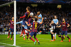 Man City Midfielder Fernandinho (BRA) heads towards goal as Barcelona Defender Gerard Pique (ESP) and Forward Alexis Sanchez (CHI) defend - Photo mandatory by-line: Rogan Thomson/JMP - Tel: 07966 386802 - 18/02/2014 - SPORT - FOOTBALL - Etihad Stadium, Manchester - Manchester City v Barcelona - UEFA Champions League, Round of 16, First leg.