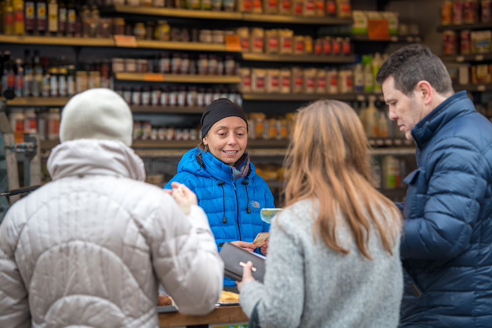 An adult female merchant helps out shoppers with their purchases, Amsterdam, Netherlands