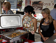 Erika Conover of Kettering (right) watches as Sarah Wilson of Dayton gets a sample for a customer at Joya's  bistro's booth during Taste of Miami Valley and Home Show in downtown Dayton, Saturday, September 18, 2010.  Joya's is about to open at The Greene.