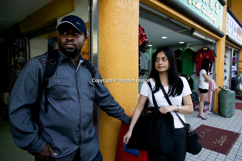 GUANGZHOU, 3. Mai , 2010:..X und seine Chinesische Frau stehen vor einem  Afrikanischen Handelszentrum in Guangzhou. X kommt aus Suedafrika, seine Mutter aus Nigeria und er selbst traeumt davon , in China eine Fabrik zu bauen.