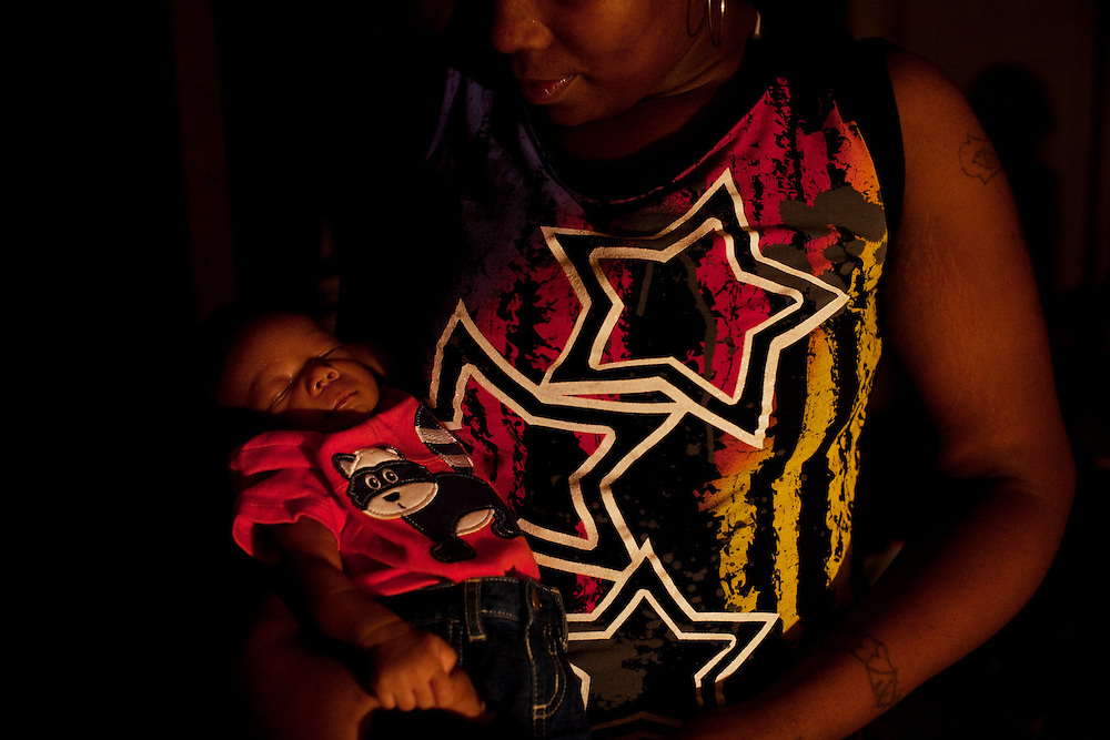 Debbie Campbell shows off her sleeping newborn son late at night in the Baptist Town neighborhood of Greenwood, Mississippi on Friday, September, 24, 2010.