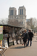 Tourists stroll along the left bank of the Seine River in Paris in front of Notre Dame