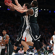 Evan Nolte, Virginia, drives to the basket while challenged by Branden Dawson, Michigan, in action during the Virginia Cavaliers Vs Michigan State Spartans basketball game during the 2014 NCAA Division 1 Men's Basketball Championship, East Regional at Madison Square Garden, New York, USA. 28th March 2014. Photo Tim Clayton