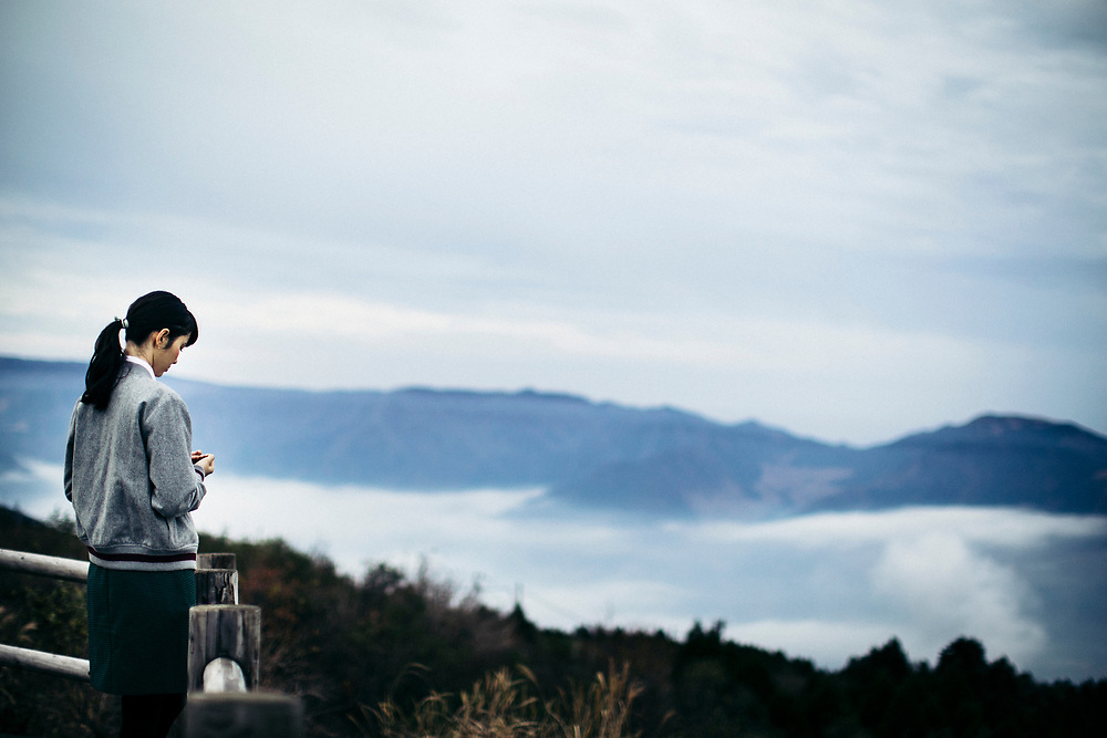 A young woman and a misty mountain landscape near Mount Aso in Kyushu, Japan.