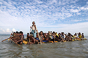 Sunday 12th November 2017. A Rohingya elder stands gracefully with staff in hand, giving direction. Men row steadily, without so much as a glance in the direction of a small group of photographers wading out to greet them.<br />