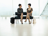 Businesswomen Sitting legs crossed on Bench in airport before flight
