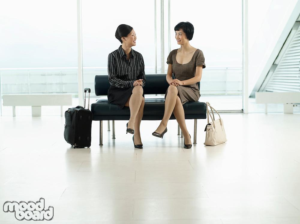 Businesswomen Sitting legs crossed on Bench in airport before flight