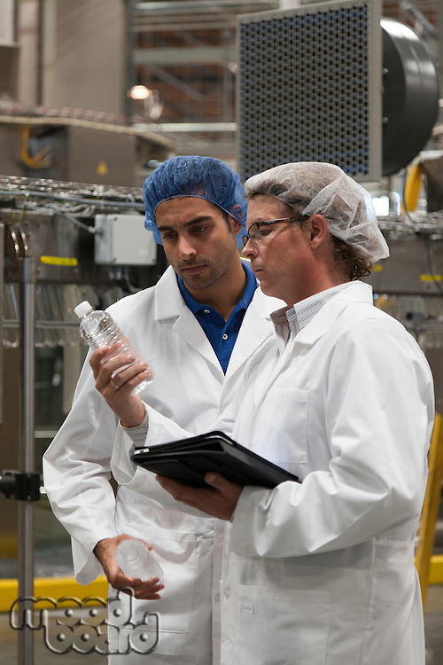 Factory workers inspecting bottled water at bottling plant