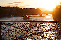 Lovers' locks on the Pont des Arts, a foot bridge over the Seine, with le Pont Neuf and Ile de La Cite in the background