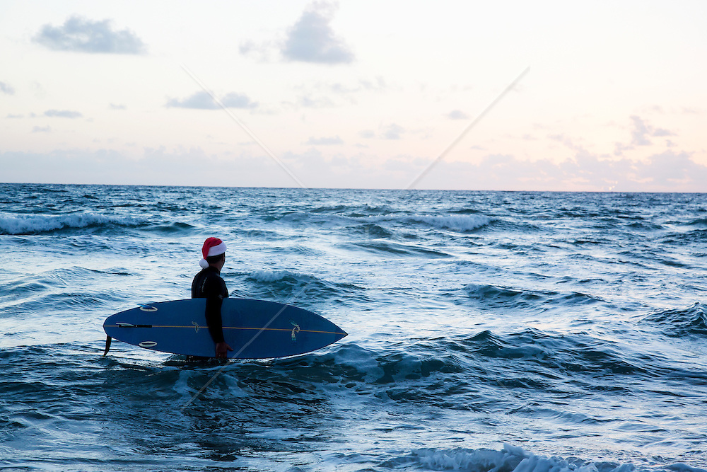 surfer with a Santa hat on standing in the ocean with a surfboard