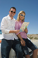 Portrait of young couple with map, leaning on car