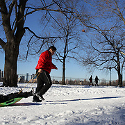 A man pulls a boy on a sled in Central Park after New York City was hit with over 7 inches of snow during its first winter storm of the year. Central Park, Manhattan, New York, USA. 4th January 2014 Photo Tim Clayton