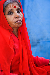 A seriously solemn stare captured in a portrait of an older women in bright red sari, Jodphur, Rajasthan, India