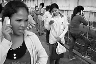 CAMBODIA. Phnom Penh. 11/01/2011: Garment workers use hired cellphones to make 200 riel ($0.05) calls to families back in their villages after their shift ends at a factory in the Tuol Sangke area. The status of young women is changing as they become the main income generators for rural families.