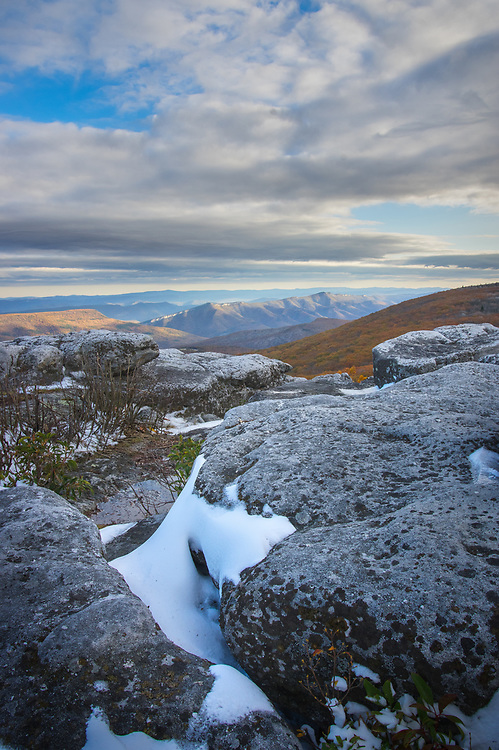 Snow hides in the crevices of the windswept rocks of Dolly Sods, revealing a path carved between mountains bridged by the remnants of autumn; the second peak, North Fork Mountain shown by the low evening sun, meets the low hanging clouds tracing a continuing path upward and skyward.