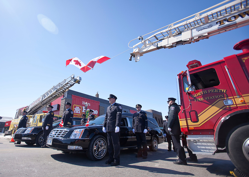 Fire fighters escort hearses carrying their fallen colleagues Kenneth Rae and Raymond Walter during a funeral procession in Listowel Ontario, Thursday, March 24, 2011. The men were killed fighting a blaze in a dollar store last Thursday when the roof collapsed.<br /> THE CANADIAN PRESS/ Geoff Robins