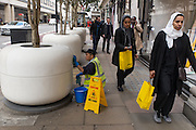 Cleaner and Middle-East clients with bags from Selfridges outside the Oxford street most famous retail store.