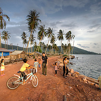 Photographer enjoys the attention of young children in small fishing village near Sihanoukville, Cambodia