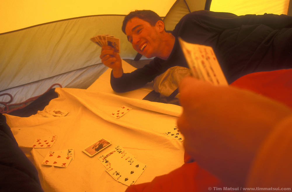Dan Aylward plays cards while tent-bound in a storm in the North Pickets, North Cascades National Park.