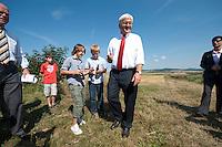07 AUG 2009, OSTHEIM/GERMANY:<br /> Frank-Walter Steinmeier, SPD, Bundesaussenminister und Kanzlerkandidat, nachdem er zwei Jungs eine Flasche Bionade signiert hat, auf dem Naturlandbetrieb Martin Ritter waehrend dem Besuch der Firma Bionade GmbH im Rahmen der Sommerreise zur Bundestagswahl 2009<br /> IMAGE: 20090807-01-120<br /> KEYWORDS: Sommerreise, Wahlkampf, Bundestagswahl 2009, Biohof, Jugend, youth