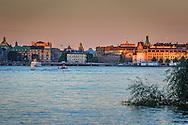 Båtar vid skymning på Riddarfjärden med Riksdagshuset och Rosenbad i Stockholm