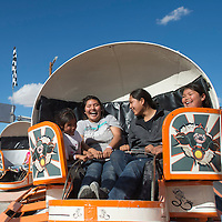 From left, siblings Shiona Austin, Dallas Austin, Tyler Austin and Zalandra Austin laugh as they ride one of the attractions at the Northern Navajo Nation Fair in Shiprock Saturday.