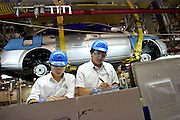 Factory workers record production details as a car body passes overhead, on the assembly line at the Shanghai GM factory in Pudong October 14, 2004.