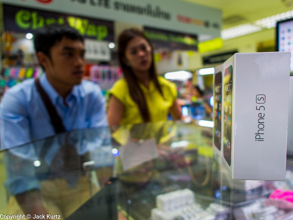21 SEPTEMBER 2013 - BANGKOK, THAILAND: A woman (in yellow) buys a new iPhone 5c in an electronics shop in MBK in Bangkok. Customers around the world lined up Friday to pick up Apple's new flagship iPhone 5s and its lower cost, more colorful brother, the iPhone 5c. The phones went on sale in the US and select countries beyond the US on Friday. The iPhone 5s and iPhone 5c will not be officially released in Thailand until late 2013 but the phones are available through the unofficial grey market in MBK, a huge shopping complex in Bangkok with dozens of small electronics shops. Early purchasers in Thailand pay a premium for the new iPhones, the top of the line iPhone 5s with 64 gigabytes of memory is about 38,500Baht, more than $1,200 (US).      PHOTO BY JACK KURTZ
