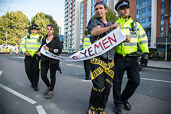 London, UK. 7 September, 2019. Metropolitan Police officers push activists holding a banner reading 'O Yemen' out of the road as a vehicle approaches ExCel London on the sixth day of Stop The Arms Fair protests against DSEI, the world's largest arms fair. The sixth day of protests was billed as a Festival of Resistance and included performances, entertainment for children and workshops as well as activities intended to disrupt deliveries to ExCel London for the arms fair.