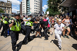 "© Licensed to London News Pictures . 07/07/2018 . Leeds , UK . Police clash with anti-fascist counter demonstrators attempting to block the path of an anti-Islam march by supporters of jailed EDL founder Tommy Robinson , which includes those from the "" Yorkshire Patriots "" and "" First for Britain "" , in Leeds City Centre . Robinson ( real name Stephen Yaxley-Lennon ) was convicted of Contempt of Court in May 2018 after committing a second offence , whilst serving a suspended sentence for the same crime . Photo credit : Joel Goodman/LNP"