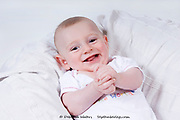 Close up of the face and hands of a laughing smiling baby boy, UK