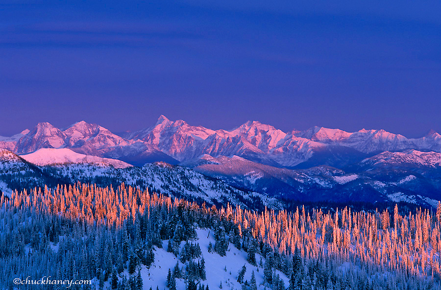 Looking to peaks in Glacier National Park from the summit of Big Mountain at sunset in Whitefish Montana