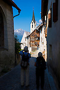 Tourists in village of Guarda in the Lower Engadine valley old world charm and painted stone 17th Century buildings, Switzerland