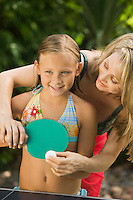Mother teaching daughter (5-7) to play ping-pong outdoors.